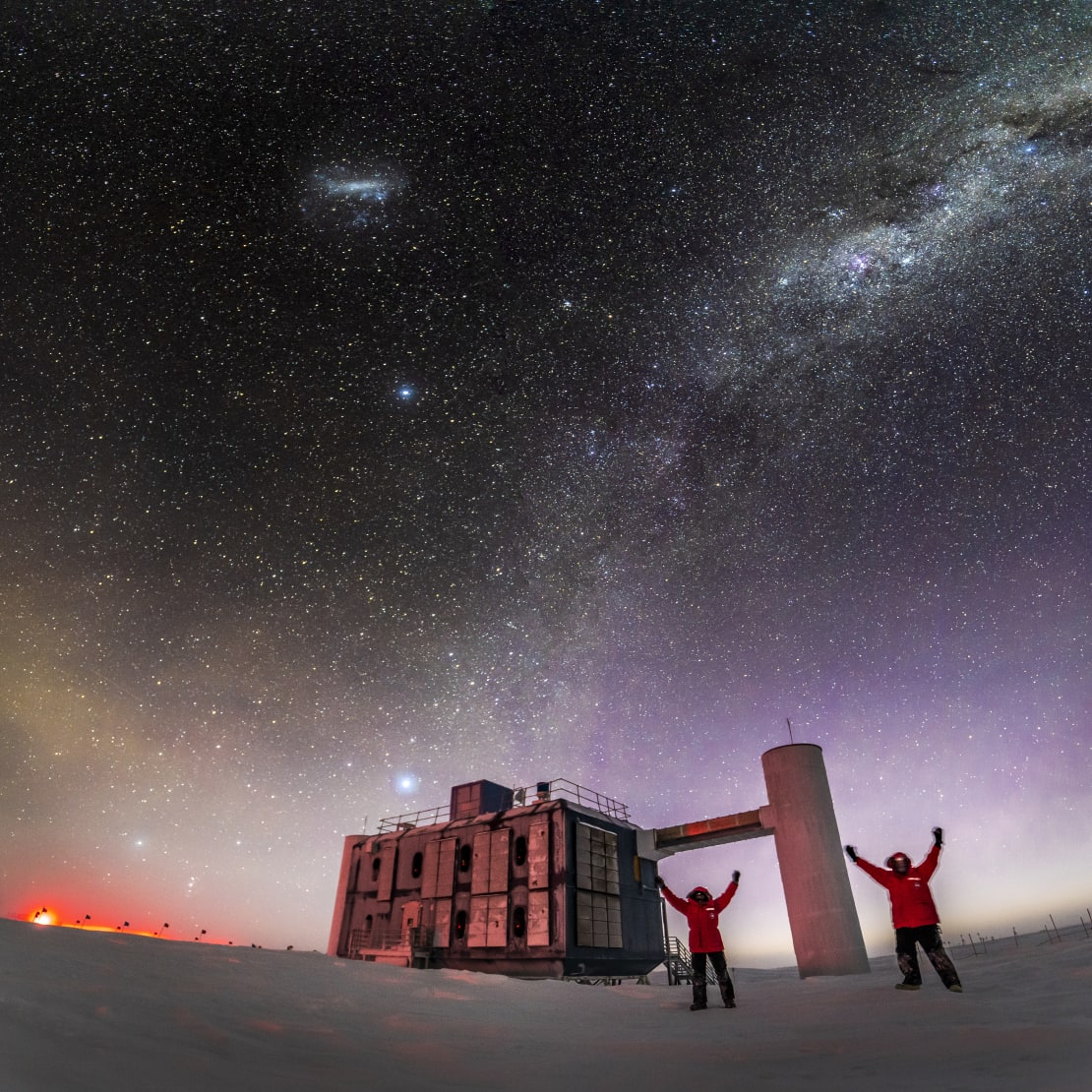 Winterovers Martin and Josh taking selfi outside the IceCube Lab, with arms up, stars in sky and sunlight along horizon.