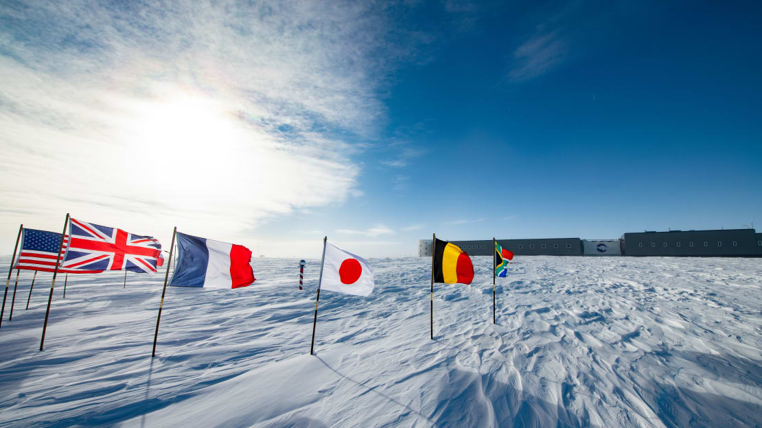 Flags around the ceremonial South Pole with the South Pole station in the background