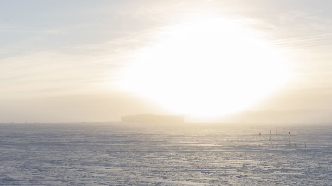Bright sun low in sky over the South Pole station.