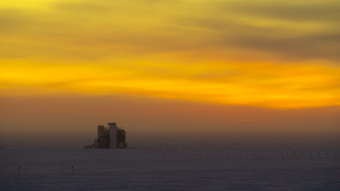 The IceCube lab at sunset, with orange cloud-filled sky.