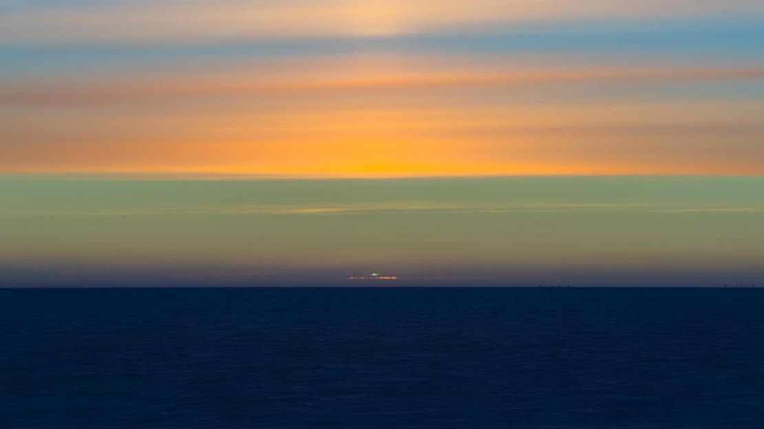Sun's green flash visible at sunset, with colorful cloud-filled sky.