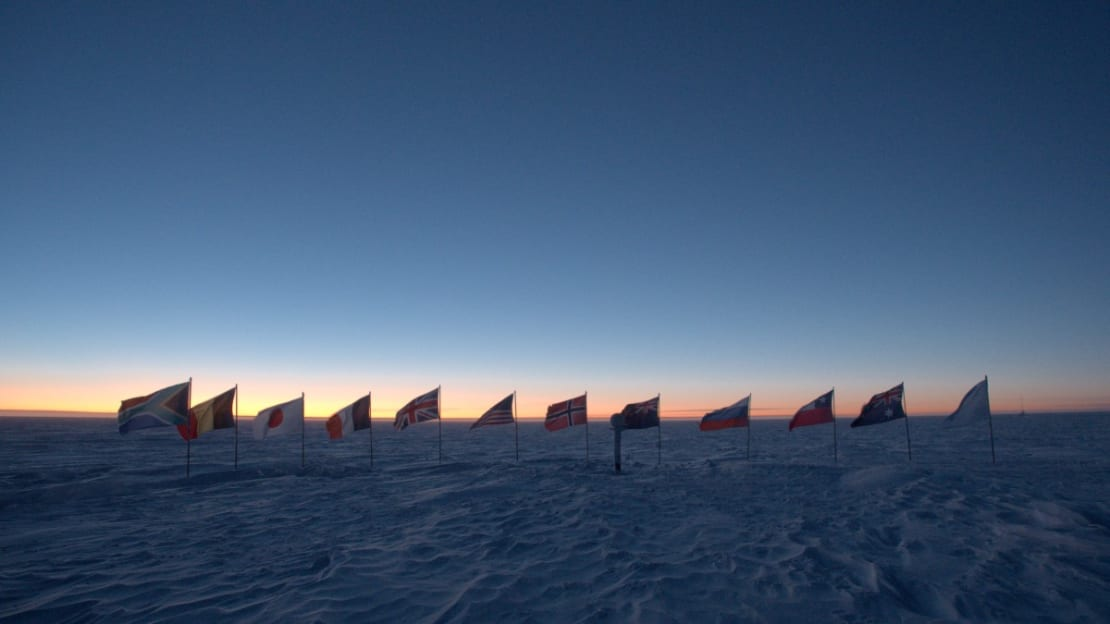 The flags at the ceremonial pole shown in shadow against a colorful horizon.