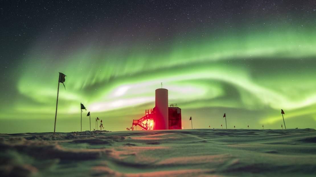 Side view of IceCube Lab with sky full of swirling green auroras.