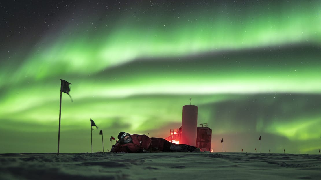Side view of IceCube Lab with person lying on side on the ice and sky full of swirling green auroras.