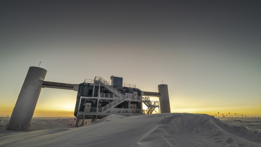 The IceCube Lab at dawn with yellow sky along horizon.