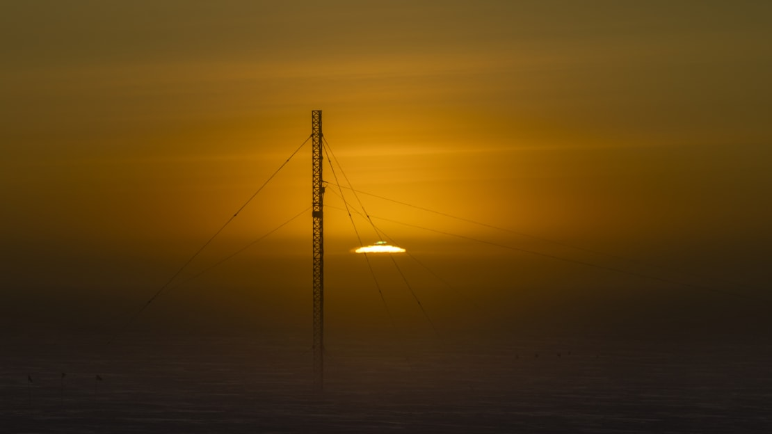 Sun rising at the South Pole, just at horizon with green flash visible, communications tower in foreground.