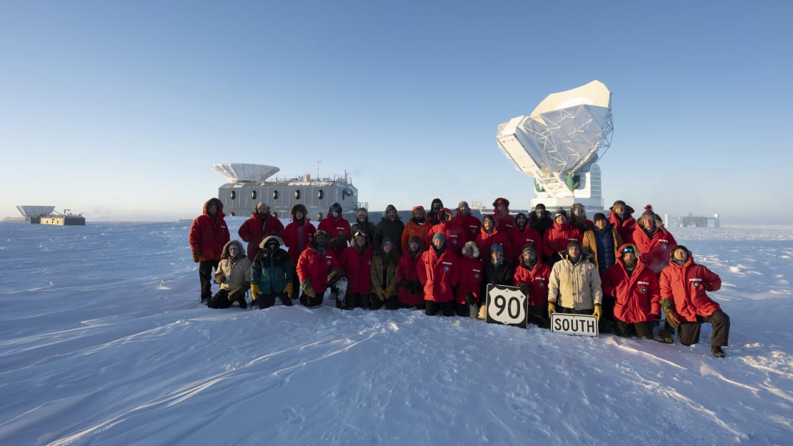 South Pole station winterovers posing as a group behind the South Pole Telescope.