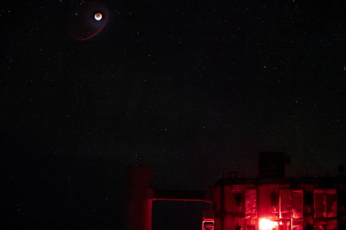 Super blood moon high in dark sky over IceCube Lab, lit in red.
