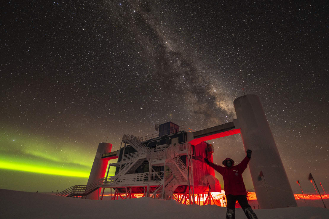 Person with arms up in front of IceCube Lab backlit by low green auroras, with Milky Way overhead.