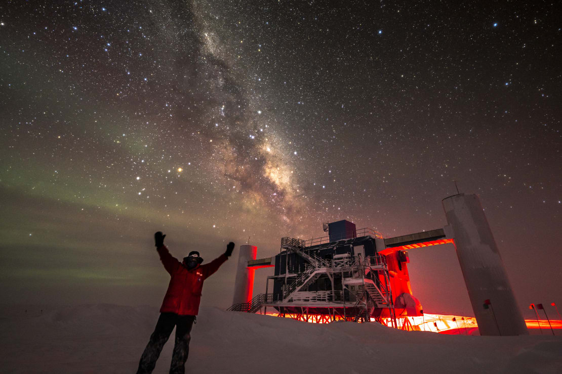 Person in red parka in front of IceCube Lab, stars and Milky Way overhead.