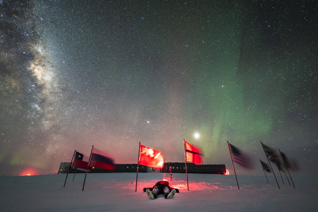 Winterover Martin lying on ground among flags at ceremonial Pole under starry skies, with view of station behind.