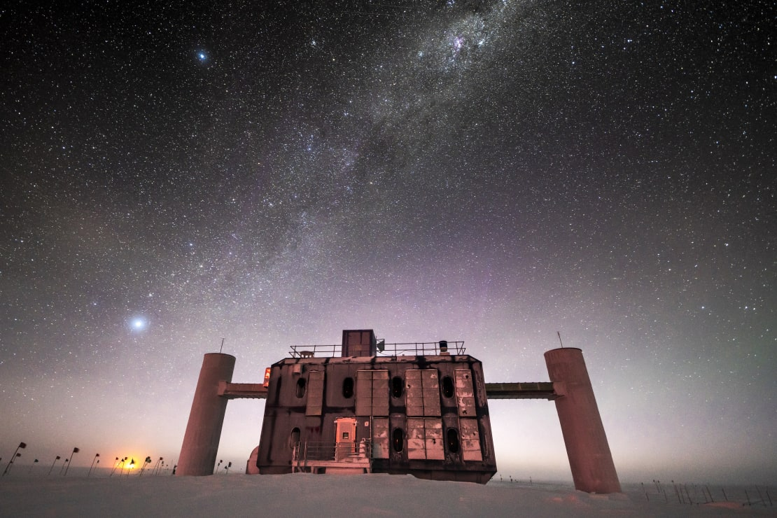 Front view of the IceCube Lab at twilight, stars in sky and sunlight just barely on horizon.