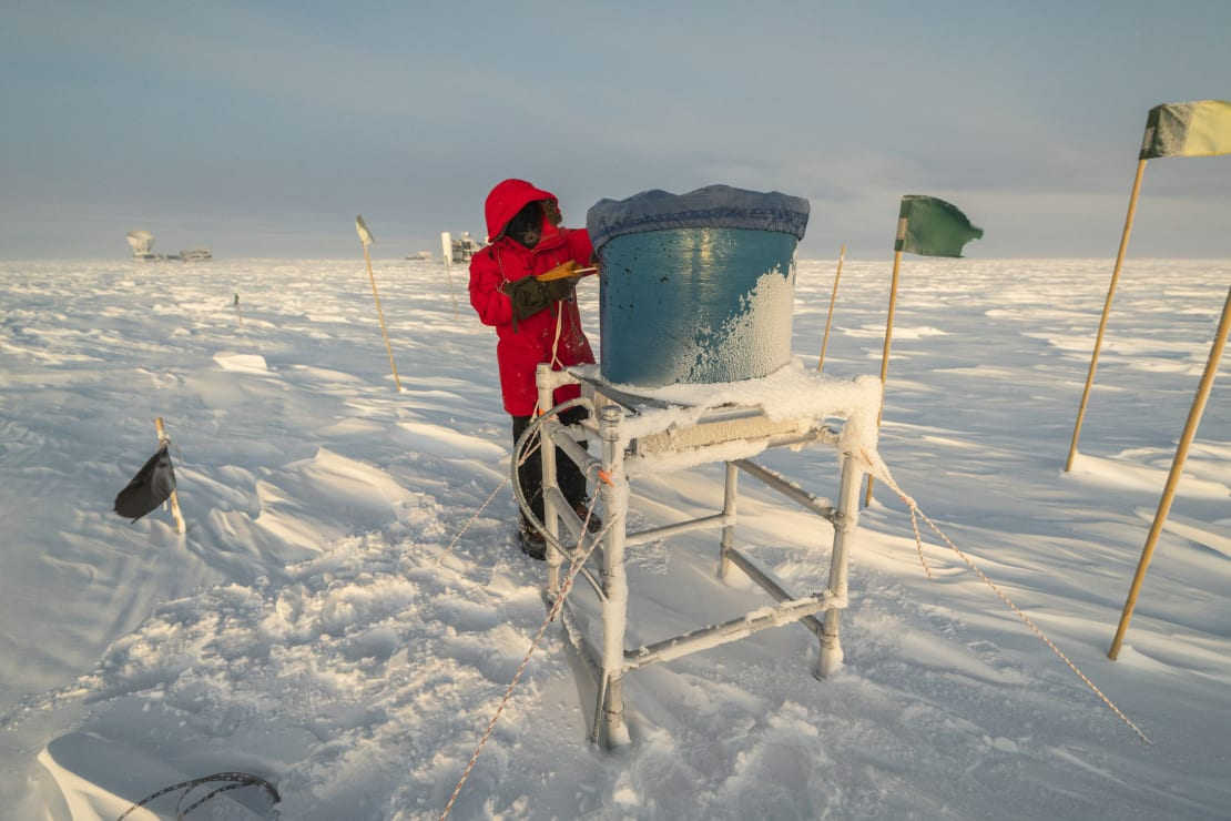 Person in red parka placing a cover on a field site IceAct telescope at the South Pole.