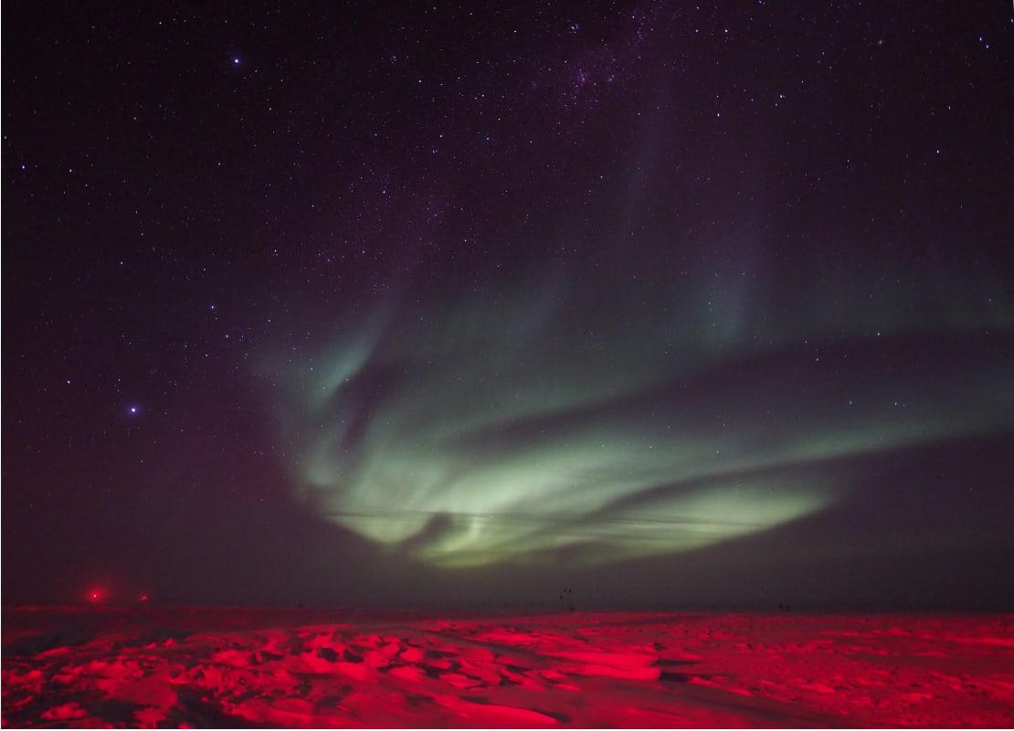 Swirling green auroras in dark sky, icy surface below lit up in red.