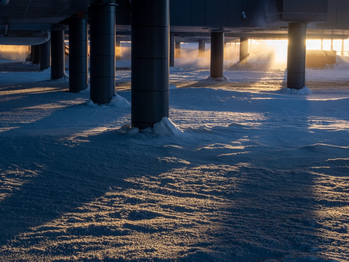 Sunlight casting shadows from behind dark columns below South Pole station.