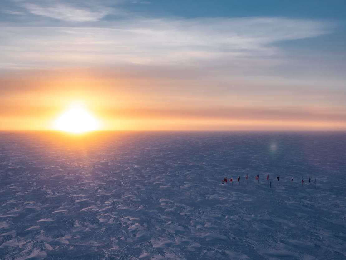 Bright sun on horizon, highlighting texture of the icy surface.