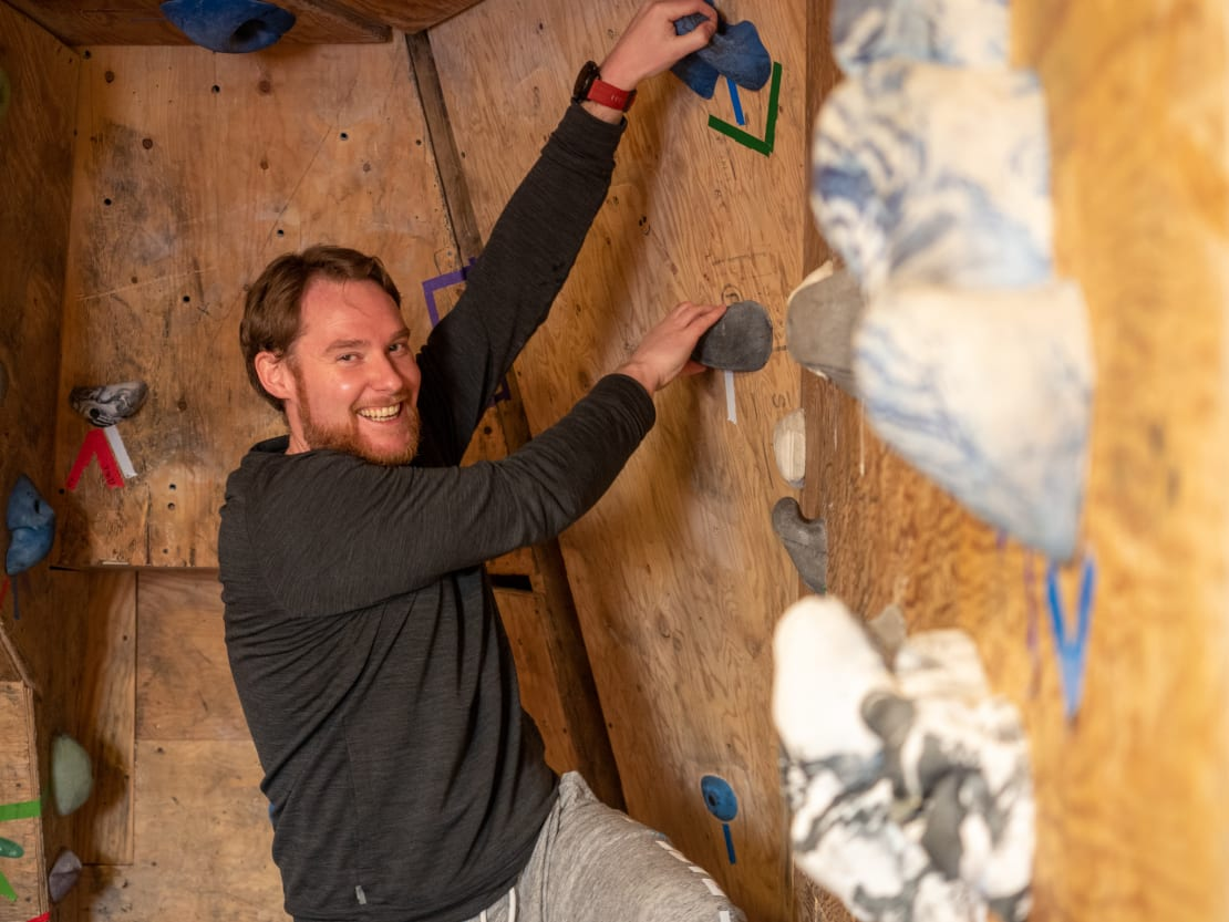 Smiling person holding onto holds of rock climbing wall.