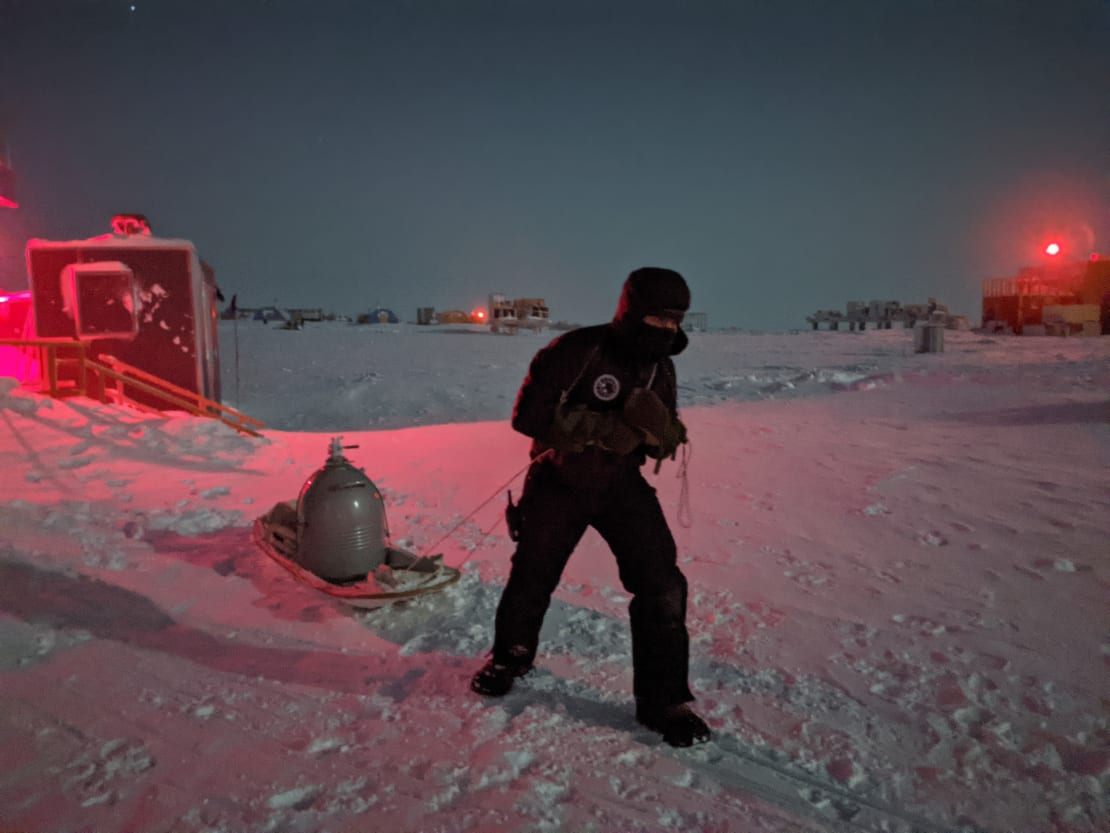 Person dragging large metal container on a sled across the snow.