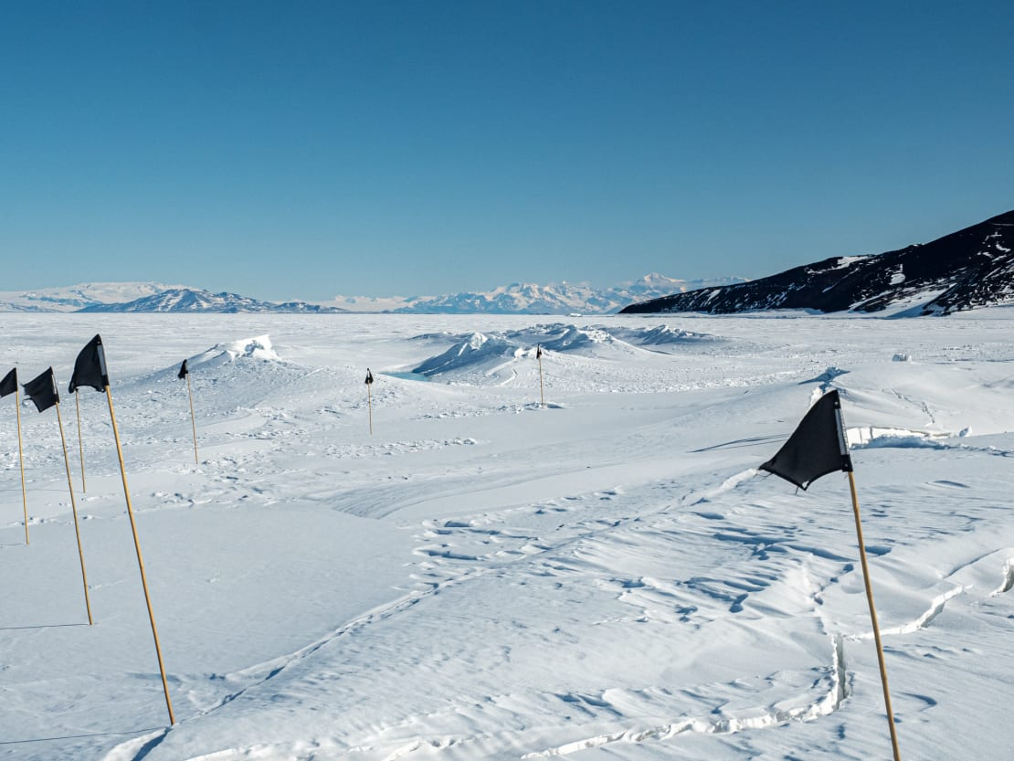 Black flags marking unsafe spots along sea ice trail.