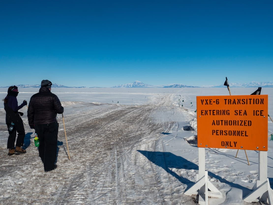 Two people at beginning of sea ice trail signed with authorized personnel only.
