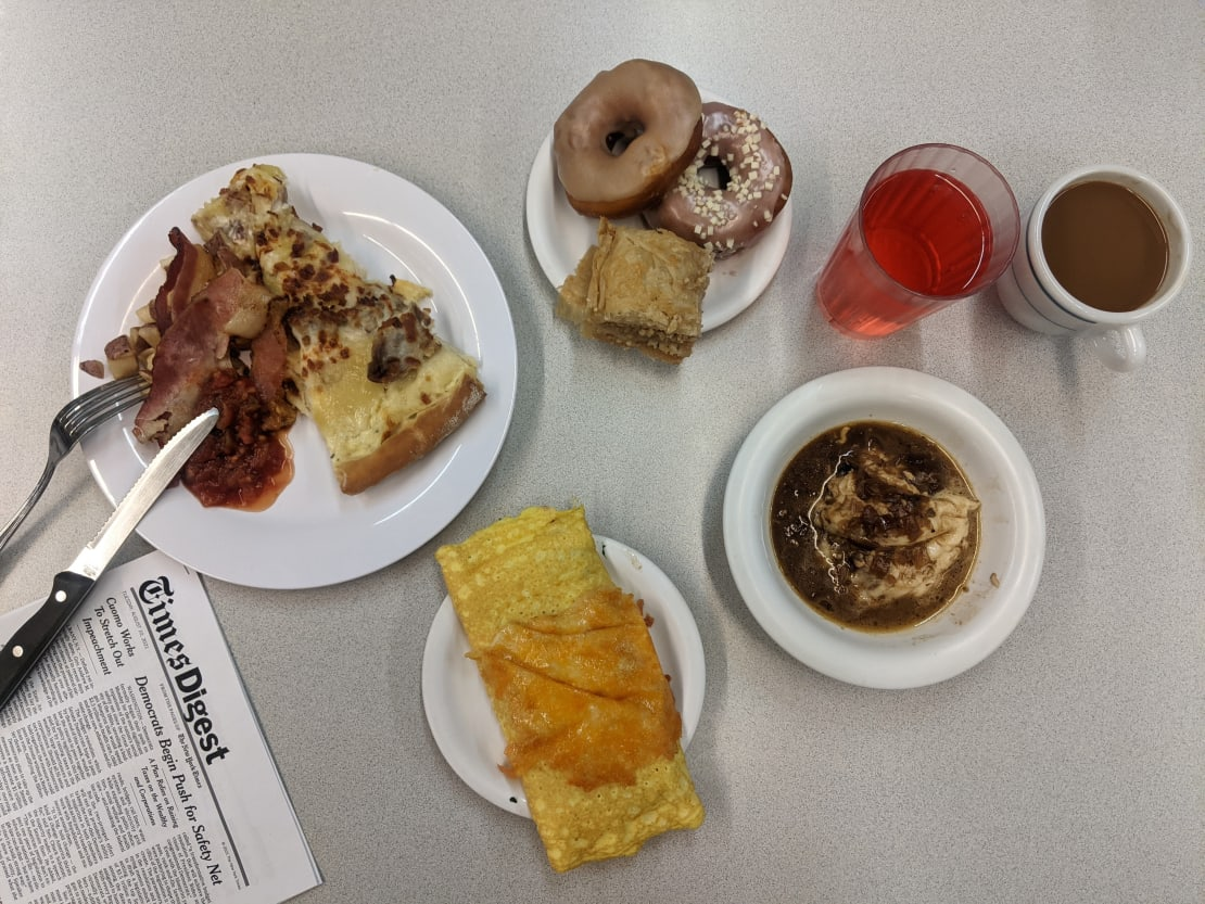 Grouping of plated breakfast items on table with utensils and newspaper.