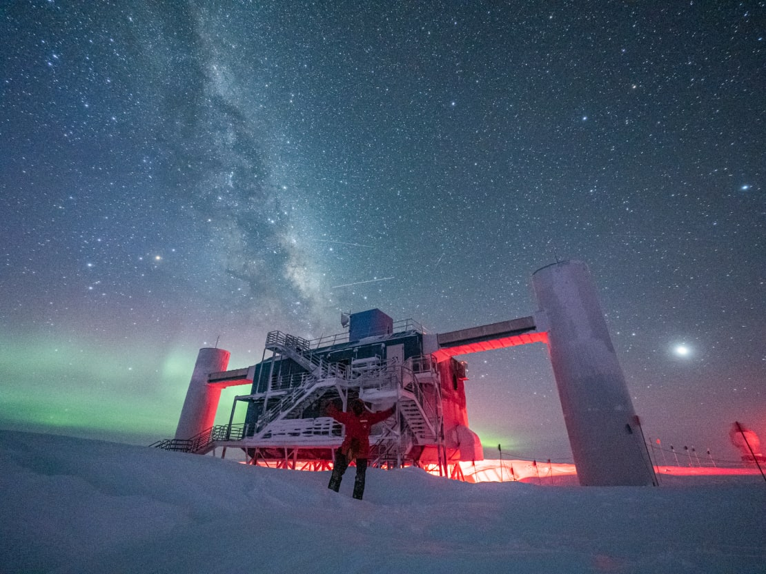 Winterover Josh with arms up, standing in front of IceCube Lab with auroras and Milky Way.