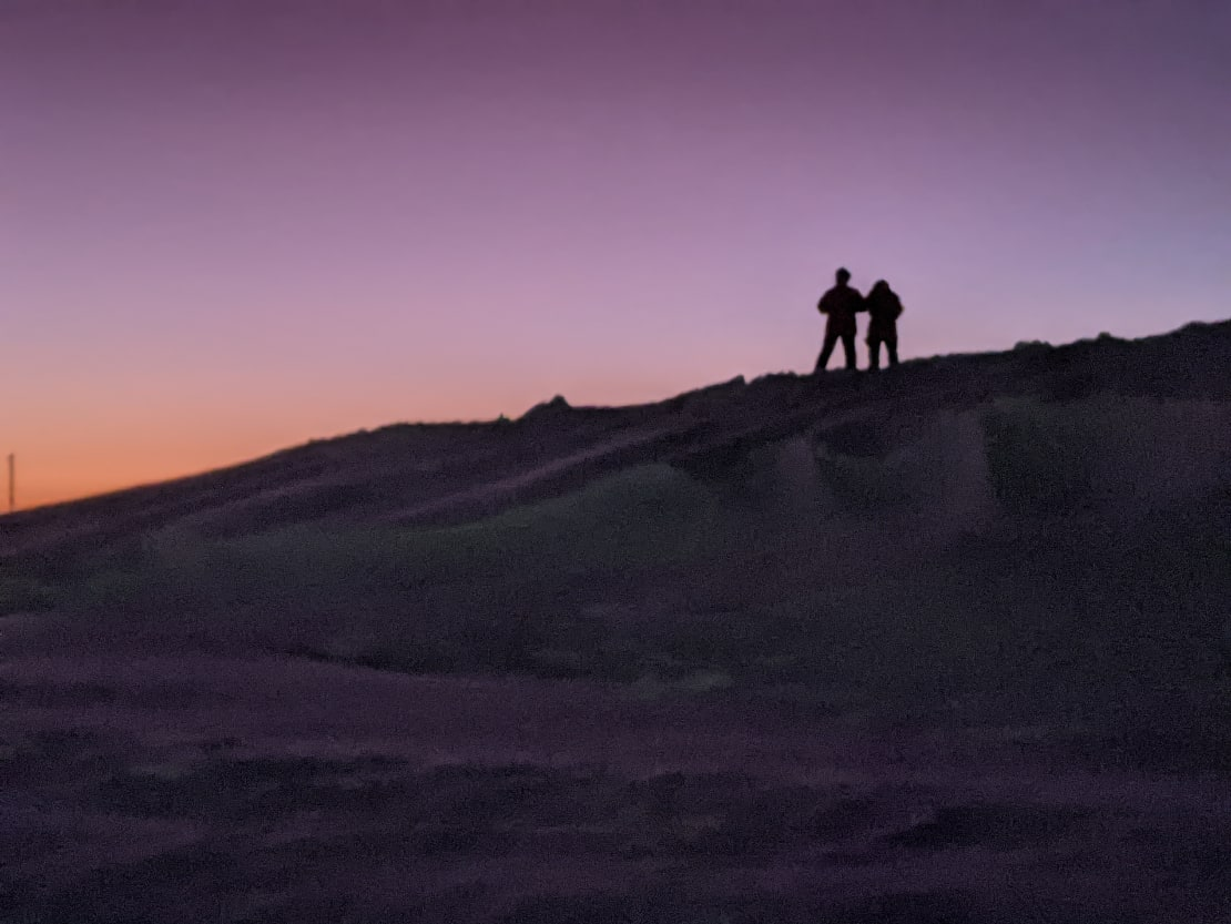 Two distant figures in shadow along ice ridge, purplish sky as background.