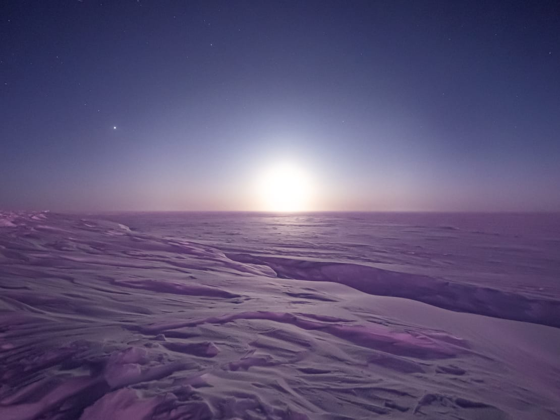 Icy barren landscape at South Pole with bright moon on horizon