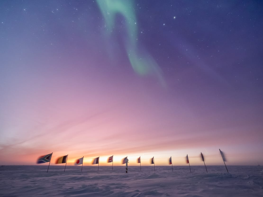 Early sunrise behind the flags at the ceremonial South Pole.
