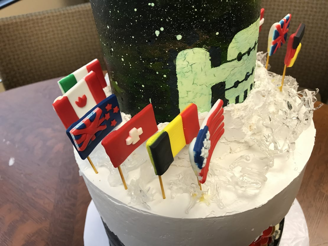 """An """"icy"""" isomalt surface and fondant flags representing the countries that are represented in the IceCube Collaboration."""