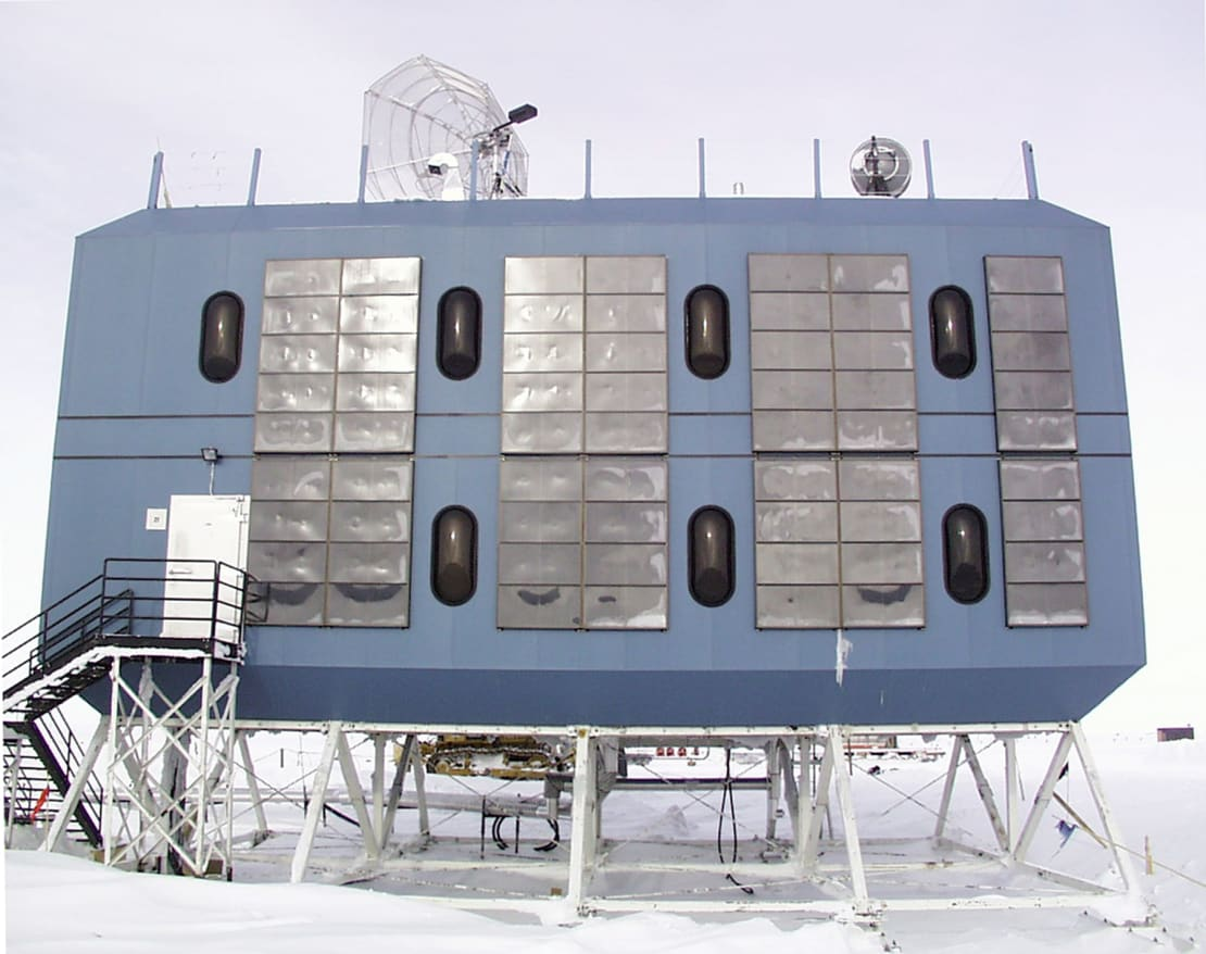 A blue, rectangular pod with 7 pill-shaped windows and a satellite dish on top. An elevated dorm at the South Pole.
