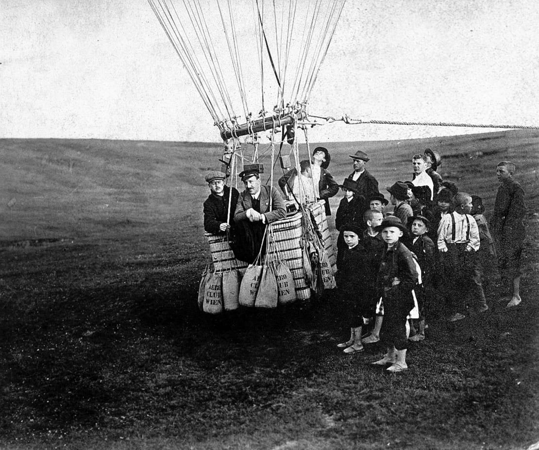 Victor Hess in a hot air balloon surrounded by onlookers.