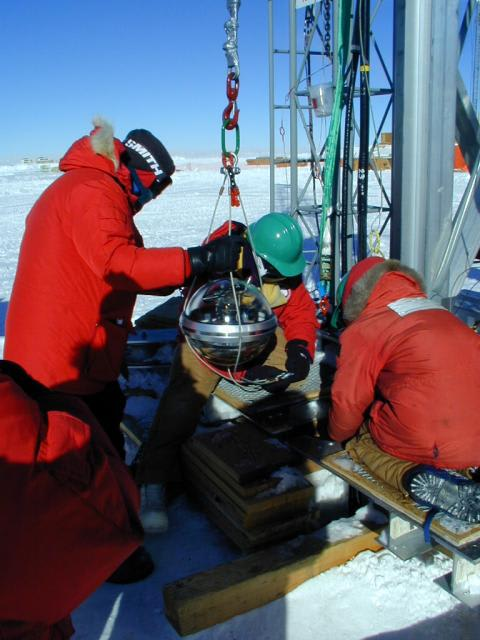 A photo of a DOM being deployed at the South Pole.