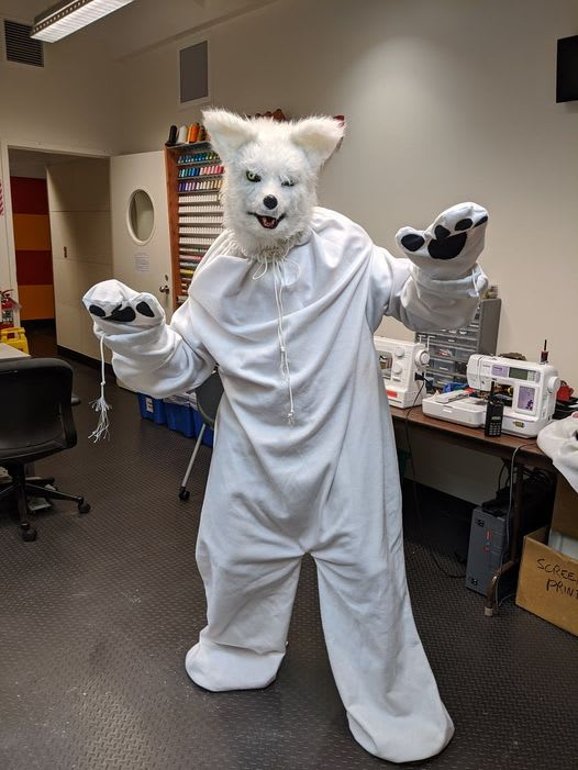 """Person standing with """"paws up"""" in white wolf costume."""