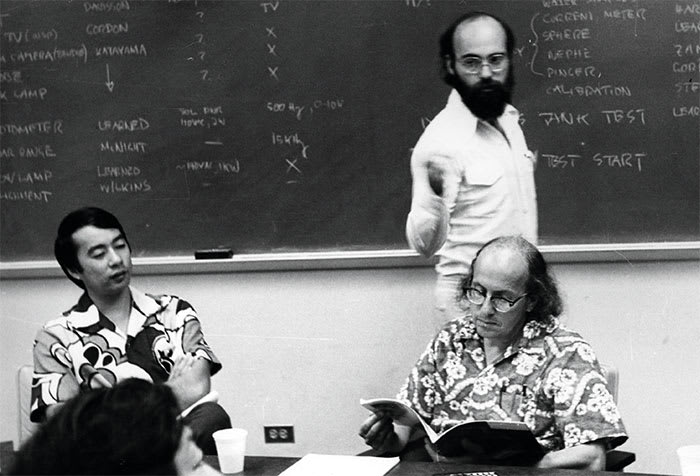 Two men in tropical shirts are seated at a table; the one on the right has glasses and is reading a pamphlet. Behind him, a man stands at a chalkboard.