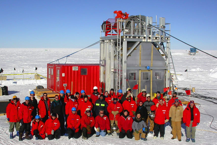 A group photo from the first season of IceCube construction at the South Pole. The group is in front of one of the towers used for drilling holes in the ice.