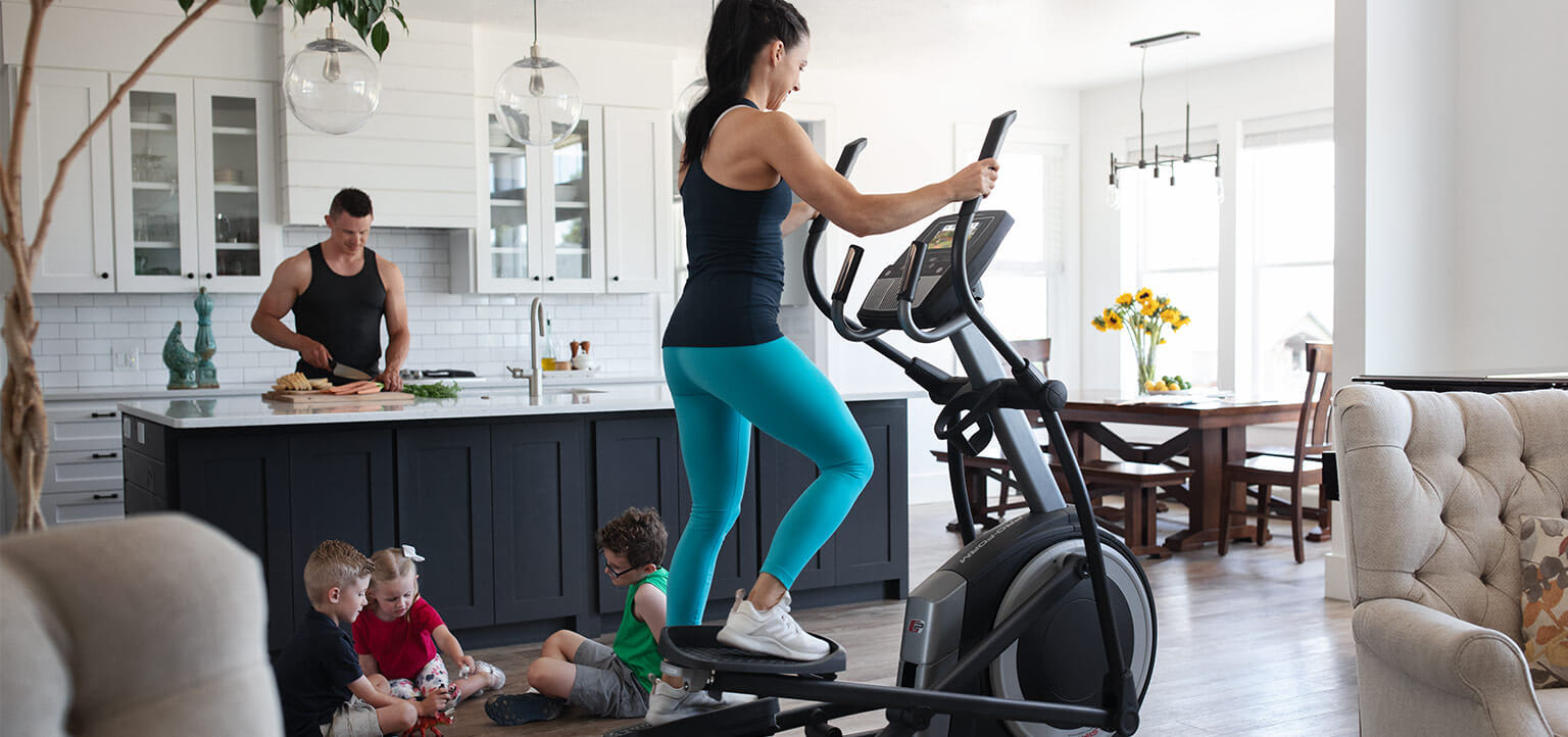 Woman riding the Carbon E7 elliptical.