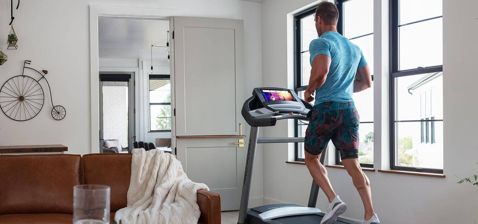 Man running on the SMART Performance 800i inside of his living room.