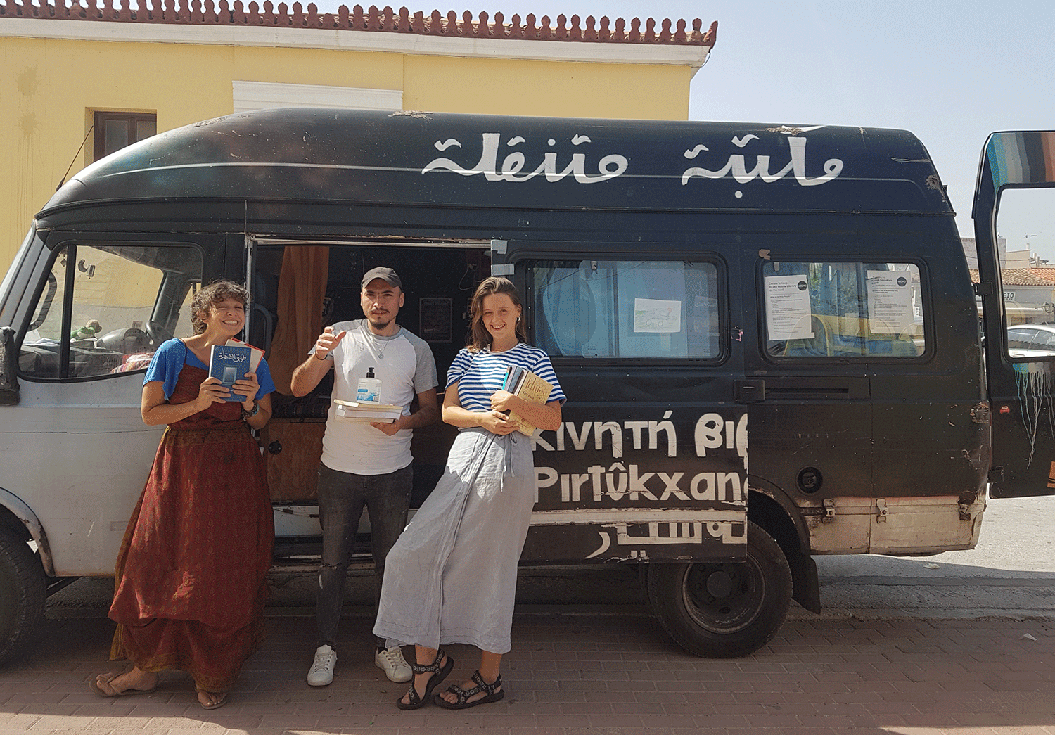 Becka, an ECHO Coordinator, left, poses with volunteer Abo Jaafar from Raqqa, Syria; and Keira, a fellow Coordinator; in front of the mobile library.