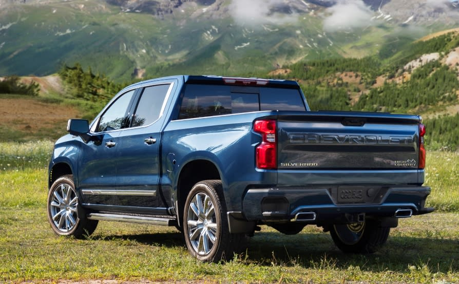 2022 Chevrolet Silverado Reveal driver rear angle in grass with mountains in background