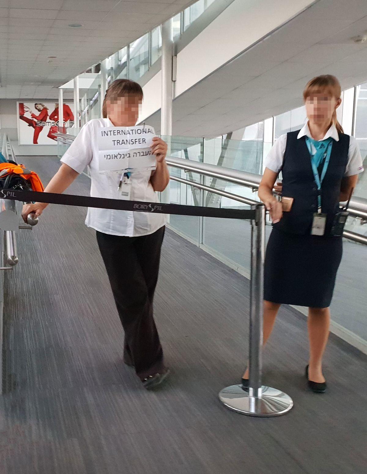 """נציגי שדה התעופה עם שלט """"International Transfer"""" לנוסעים בקונקשן"""