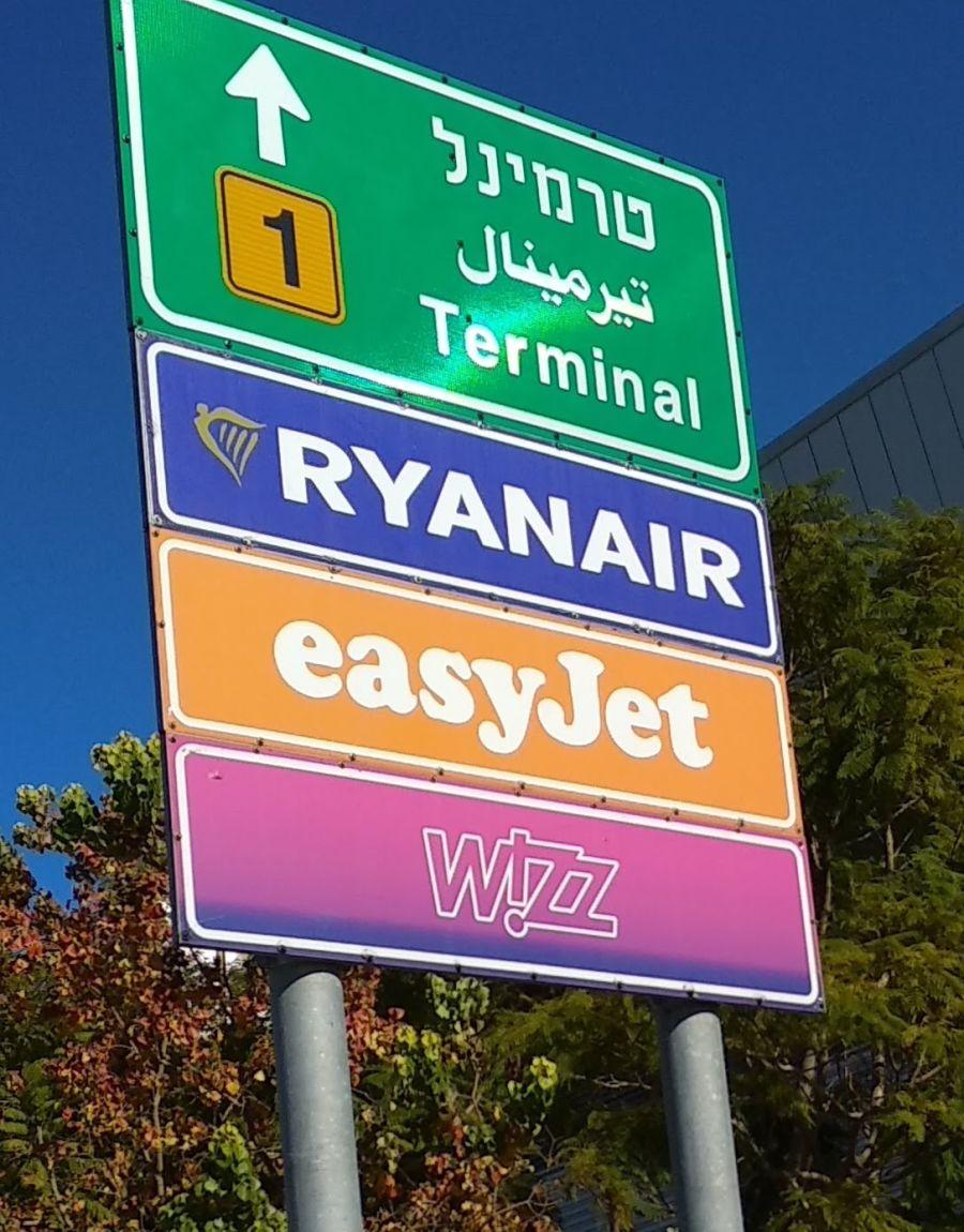 שלט הכוונה לחניה בטרמינל 1 לטסים עם Ryanair, easyJet, Wizz air - האם צריך לשלם על מזוודה?