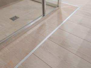 dettagli di un pavimento in materiali naturali. Legno e piastrelle certificate eco compatibili.