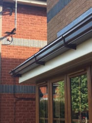 Cream roofline system with deep flow brown ogee guttering