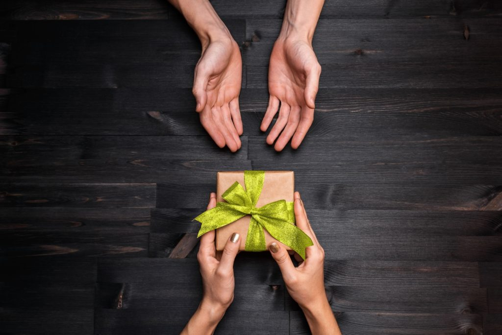 Person being rewarded a gift wrapped with a ribbon