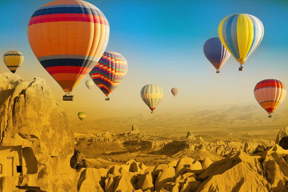 Hot air balloons over a rocky landscape