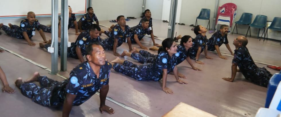 Uniformed members of the Nepalese Formed Police Unit in Haiti practicing yoga.
