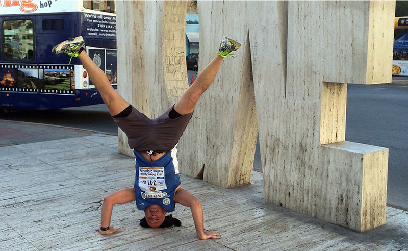 Andrew Mackay in a headstand at the LOVE statue (also upside down) in St. Julian's, Malta