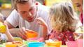 Ein Fachmann Betreuung begleitet Kinder beim Essen.