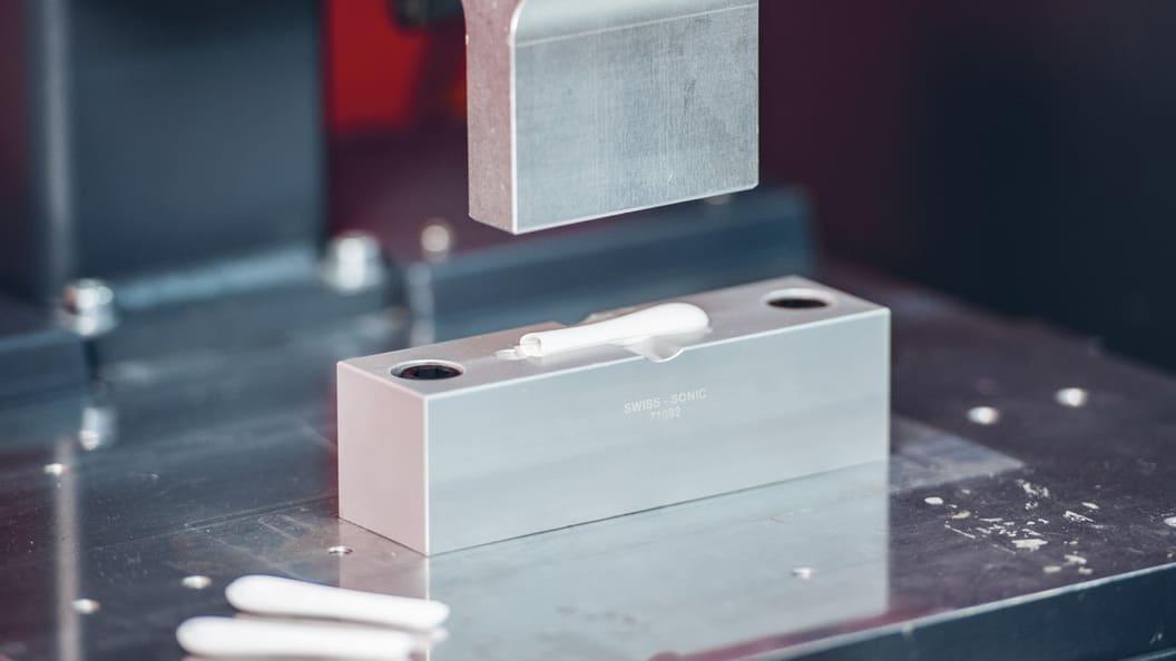 Zwei identische Bauteile werden mittels Ultraschall zu einer Schutzkappe verschweisst.